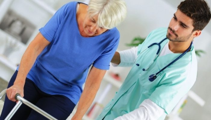 Male support worker helping older woman on walking frame
